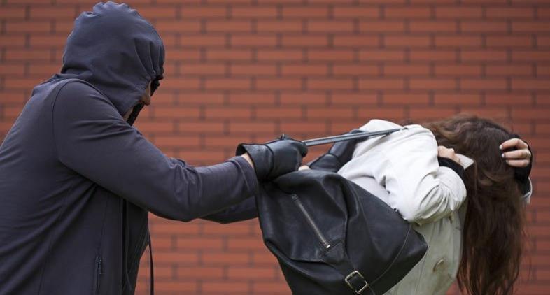 Duas pessoas em uma bicicleta praticam roubo com agressividade perto dos correios